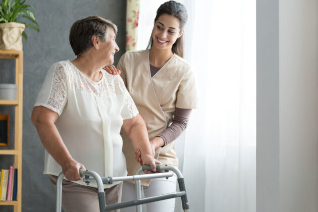 nurse helping older woman with physical therapy.